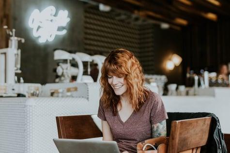 Moça alegre mexendo em um laptop