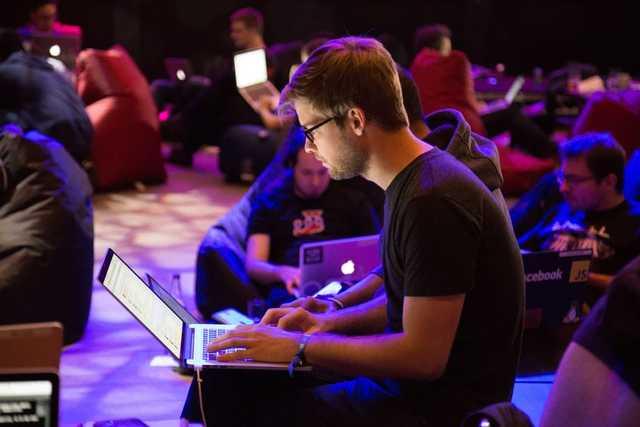 Rapaz concentrado olhando para a tela de um laptop