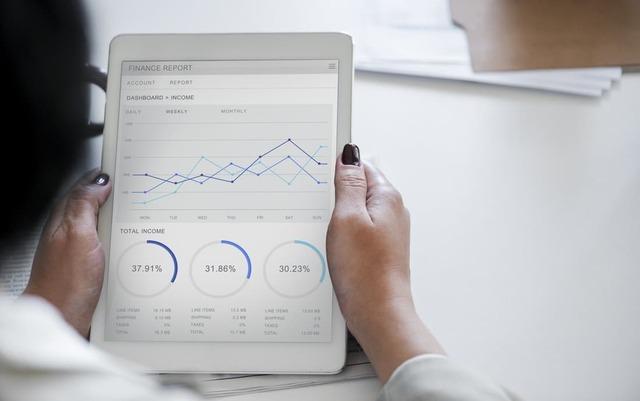 Mulher segurando um tablet com gráficos financeiros