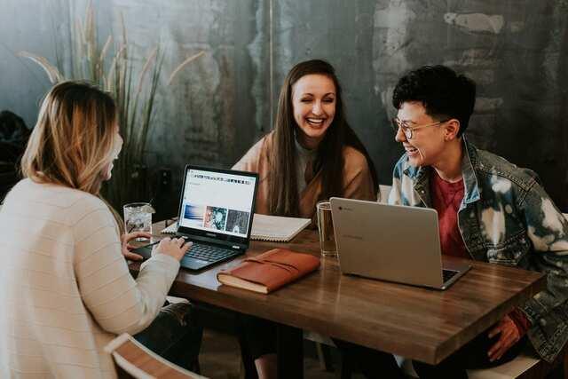 Pessoas sorridentes trabalhando em seus laptops