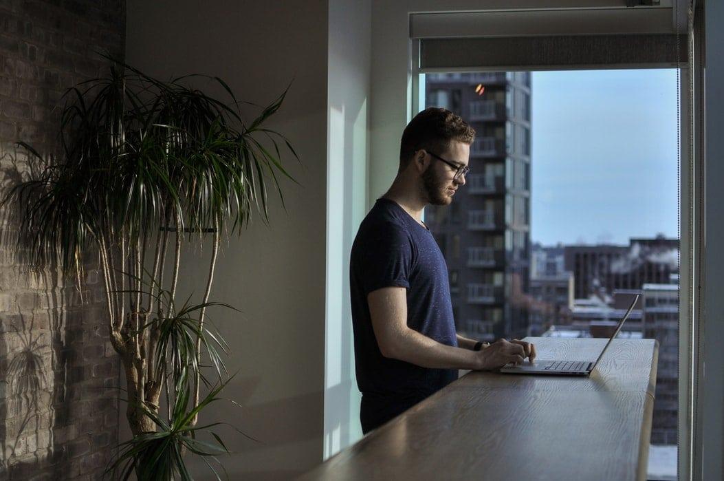 Um homem em pé em frente a uma bancada digitando em um laptop