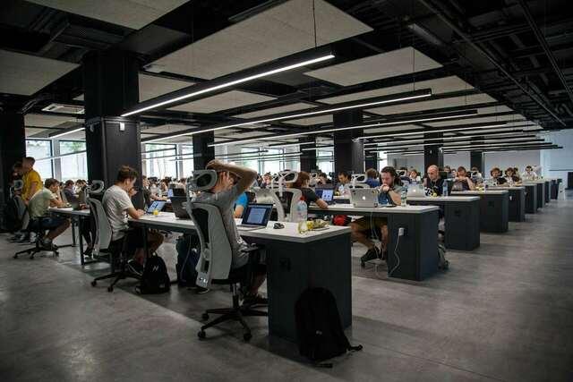 Pessoas em bancadas em um escritório com espaço aberto