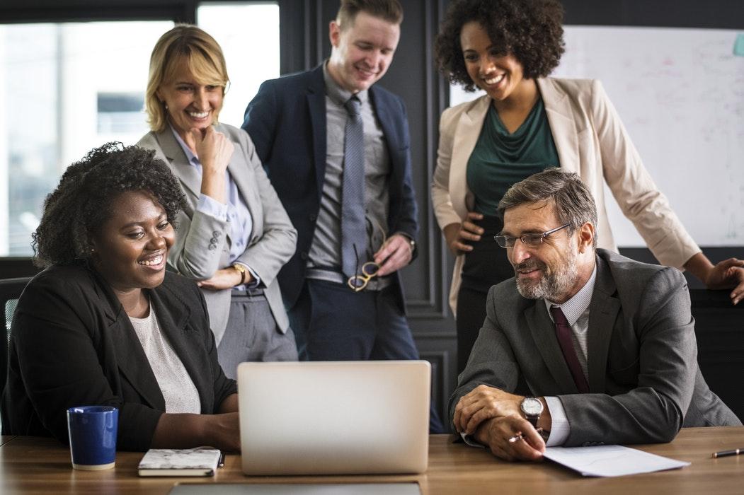Pessoas em uma sala de reunião olhando para a tela de um laptop